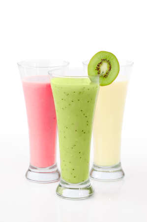 Three fruit smoothies in tall glasses on white background