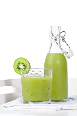 Swing top bottle and glass tumbler of kiwi smoothie on tray photo