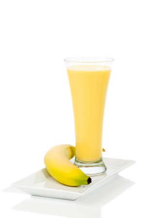 licuado de platano: Smoothie de banano en vaso sobre fondo blanco