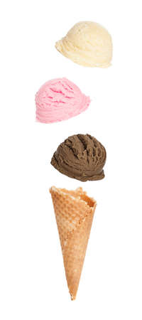 wafers: Single wafer cone with chocolate, strawberry and vanilla ice cream scoops falling onto it Stock Photo