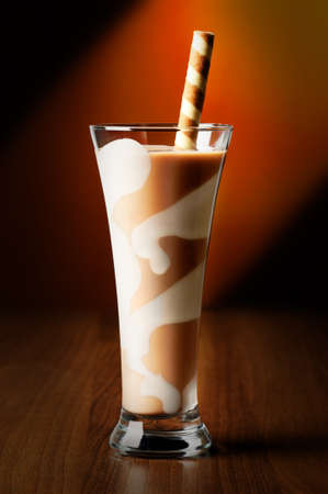 Chocolate smoothie drink in decorated tall glass with spiral wafer straw photo