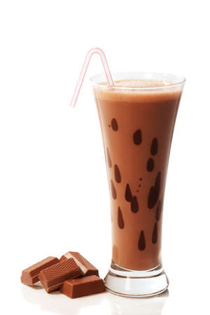 Chocolate milkshake drink in tall glass with chocolate chunks to the side