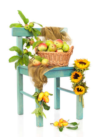 Basket of apples with sunflowers on rustic chair, white background photo