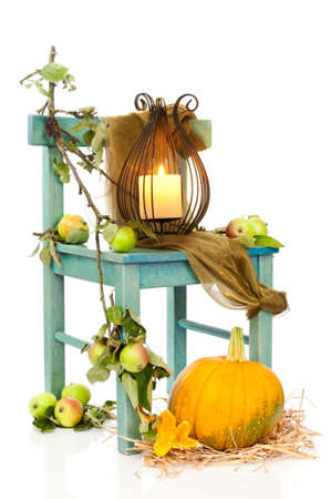 Halloween lantern on rustic chair decorated with apples and pumpkin photo