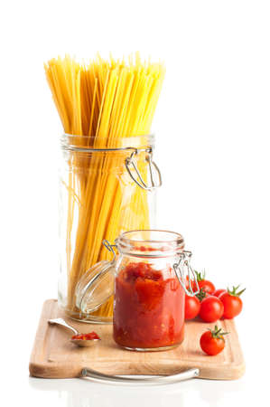 Tomatoes and spaghetti pasta in glass jars on wooden chopping board on white background