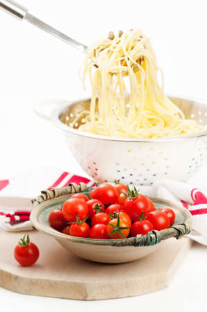 straining: Cooked spaghetti pasta in colander with ripe tomatoes