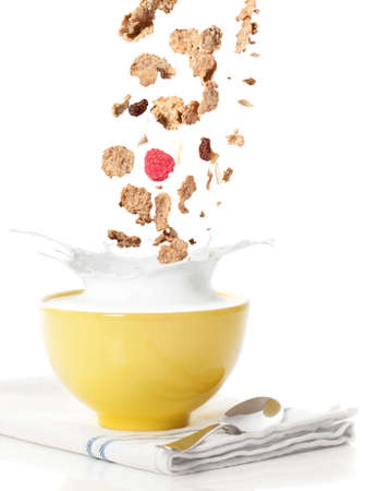 cereal bowl: Pouring healthy cereal into a bowl with milk splash Stock Photo