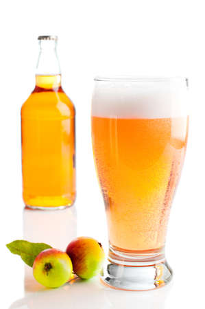 pint: Glass of cider with apples and bottle on white background
