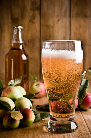 Glass of cider with apples and bottle on rustic wooden background Standard-Bild