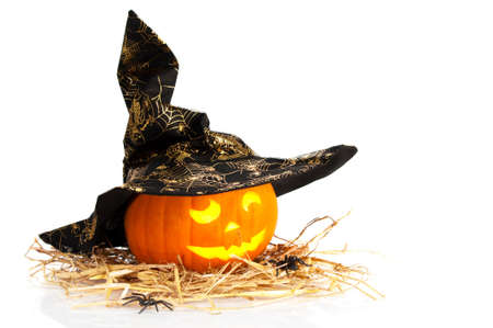 witch face: Halloween jack o lantern carved pumpkin wearing witches hat on straw with spiders and white background Stock Photo