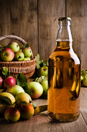 Full bottle of cider with basket of apples Standard-Bild