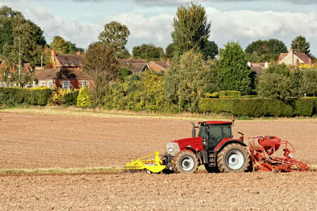 Tractor planting seeds in the autumn, countryside village in background