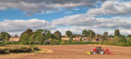 Tractor planting seeds in the autumn, countryside village in background photo