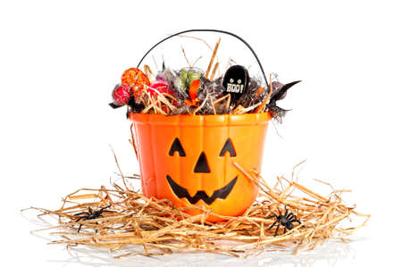 Halloween-emmer met suikergoed wordt gevuld voor trick or treat die op een bed van stro zitten