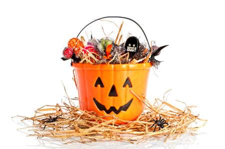treats: Halloween secchio riempito con le caramelle per trick or treat seduto su un letto di paglia