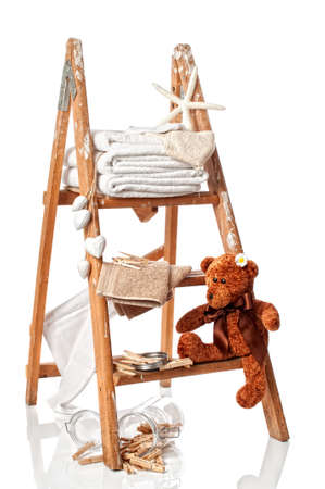 laundered: Step ladder with freshly laundered towels and clothes pegs on white background