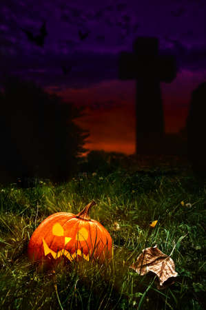 cemetry: Halloween jack o lantern in cemetery with cross in background