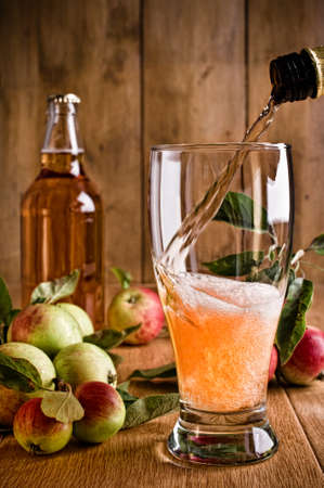 Pouring a glass of cider with apples and bottle on rustic wooden background