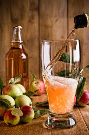 Verser un verre de cidre de pommes et de la bouteille sur fond de bois rustique