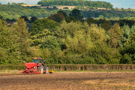 Tractor sewing seeds in autumn field photo