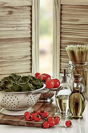 Frisch gewaschen Spinat mit Tomaten und Pasta in der Küche