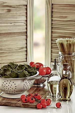 kitchen utensils: Reci�n lavadas espinacas con tomates y pasta en la cocina