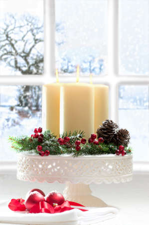 Christmas candles in the window with snowy scene in background
