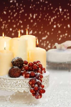 Falling snow onto Christmas still life with grapes and figs with Christmas cake in background photo
