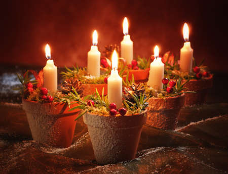 christian candle: Brightly lit Christmas candles in pretty snow covered decorated terracotta pots Stock Photo