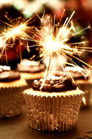 Party cupcakes decorated with chocolate ganache and sparklers Stock Photo