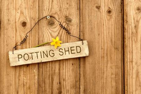 Potting shed teken op houten achtergrond met narcissen bloem Stockfoto