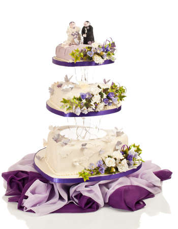 Heart shaped wedding cake in three tiers with flowers and butterflies made from sugar icing on white background photo