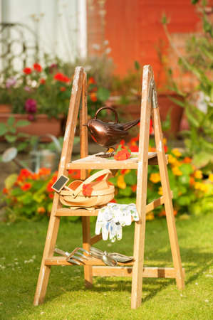 implements: English summer garden with wooden stepladders and planting implements
