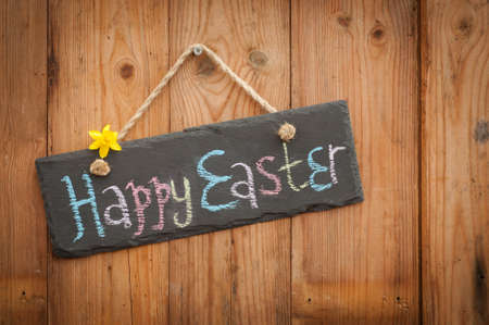 Happy Easter in colourful chalk on slate sign with wooden background Stock Photo - 10406042