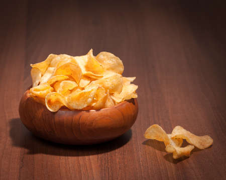 Flavoured potato crisps in wooden bowl on table photo