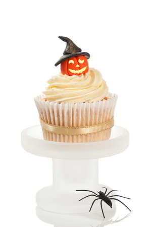 Halloween cupcake with pumpkin wearing a witches hat on a white background photo
