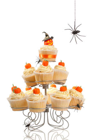 Pumpkin cupcakes for Halloween party time with spiders on white background Standard-Bild