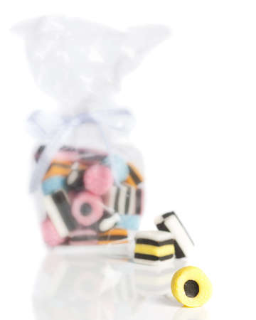 cellophane: Licorice sweets on a white background with cellophane bag of sweets in background, focus on front yellow sweet with shallow depth of field