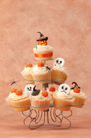Pumpkin cupcakes for Halloween on cakestand with various toppings photo