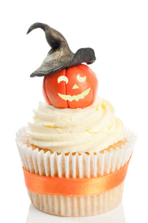 Halloween pumpkin cupcake wearing a witches hat on white background photo