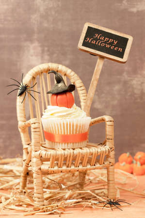 Pumpkin cupcake wearing a witches hat with Halloween holiday sign in the background photo