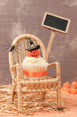 Pumpkin cupcake with witches hat with blank sign for your Halloween message photo