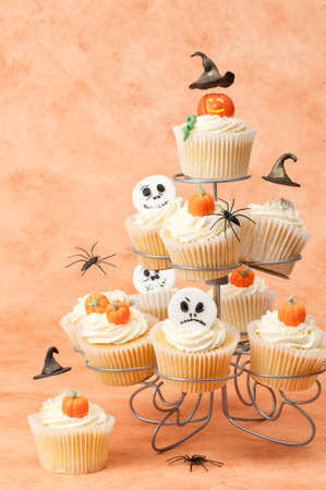 Halloween cupcakes with a selection of festive toppings including floating witches hats photo