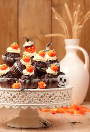 Halloween chocolate muffins on cake stand with homemade fondant pumpkins photo