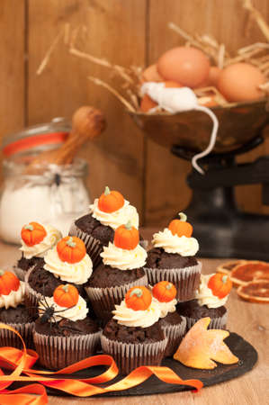 Making Halloween chocolate muffins for trick or treat night and decorating with orange sugar pumpkins photo