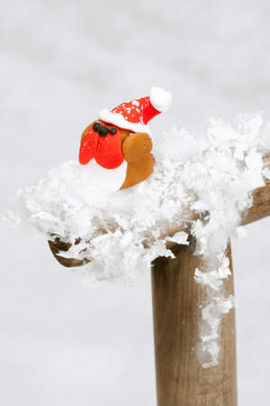 Robin made from fondant icing wearing santa hat on snowy spade handle with snow in background photo