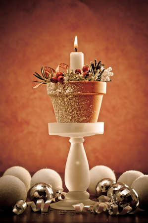 Single lit Christmas candle and baubles with festive background photo