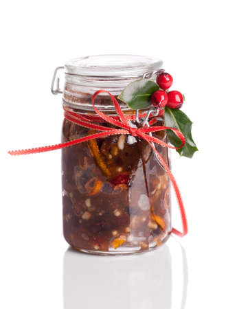 closed ribbon: Jar of Christmas mincemeat tied with a festive ribbon with holly and berries on a white background Stock Photo