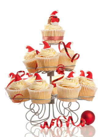 Cupcake stand filled with cakes decorated with fondant robin and santa hats on white background