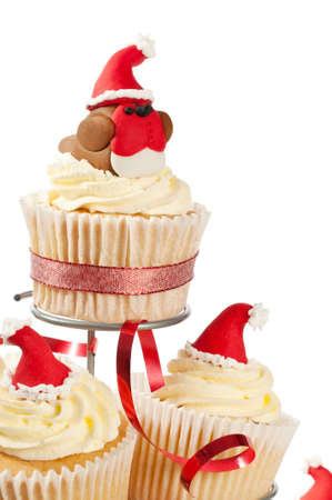 Decorated Christmas cakes on stand with fondant robin redbreast wearing a santa hat